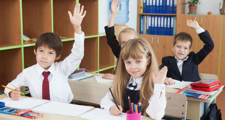 英語の授業で挙手をする子ども達
